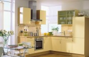 a pale yellow kitchen with wooden countertops and a neutral tile backsplash plus a glass table is very chic