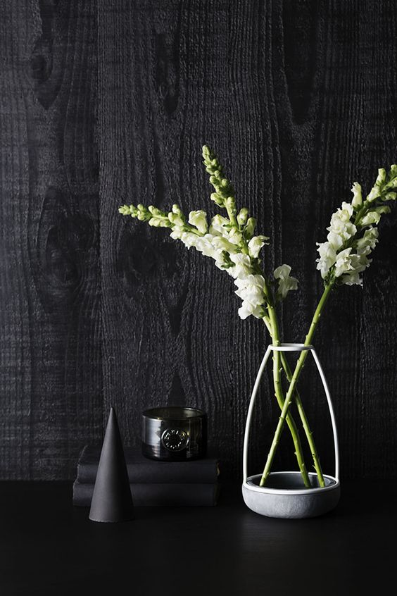 a grey frame only vase with white blooms and a catchy glass candleholder for laconic and minimal decor