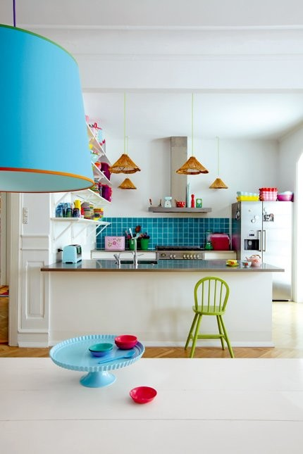 a playful kitchen with white cabinetry, stainless steel appliances, a bold blue backsplash and lamps and some colorful touches is fun