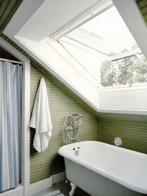 a green attic bathroom with a vintage feel, a clawfoot tub and a shower space with a striped curtain