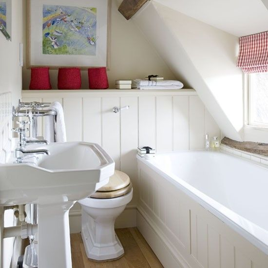 a small creamy attic bathroom done with beadboards, a free-standing sink and touches of red