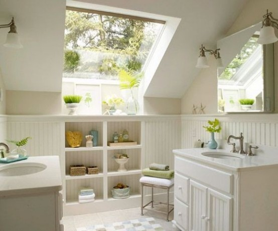 a small neutral attic bathroom with a large window, built-in storage spaces and two vanities