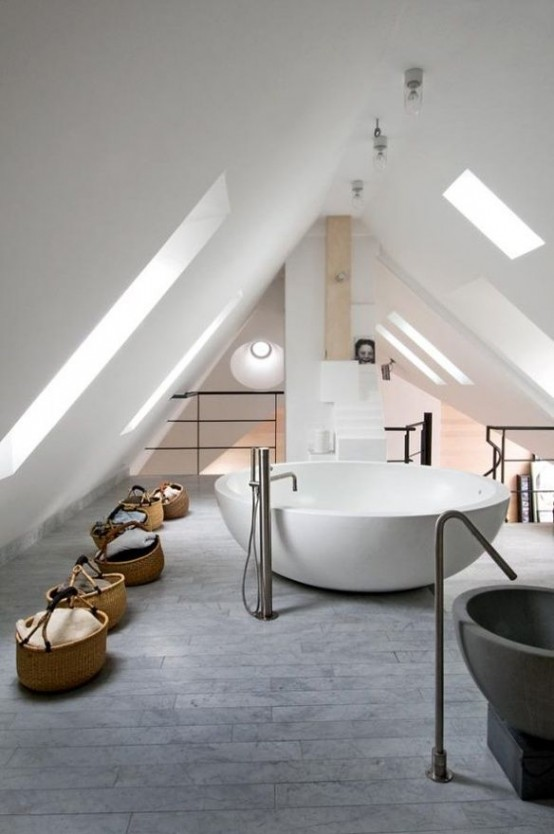 a contemporary attic bathroom with a grey tile floor, a large round tub and some baskets for storage