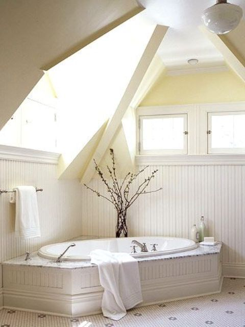 a creamy bathroom with skylights, a built-in bathtub and a branch arrangement in a vase