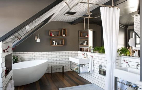 an industrial-inspired attic bathroom with grey walls, white subway tiles, an oval tub, a shower space and two sinks