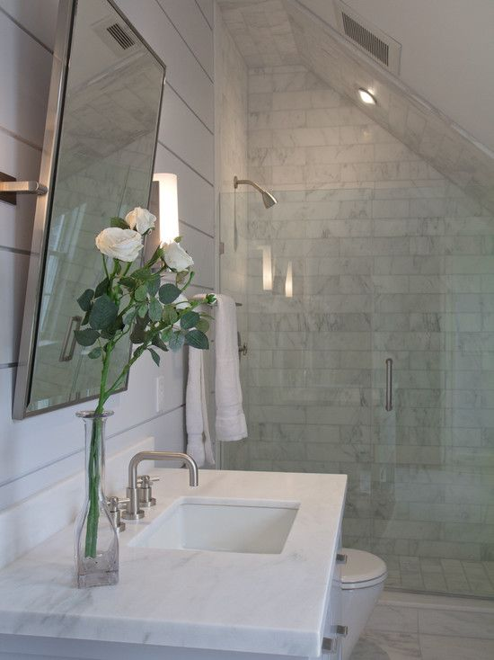 a small marble attic bathroom with a square marble sink and a small shower space