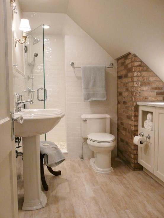 a small attic bathroom with a brick wall, white tiles, a free-standing sink and a floating vanity