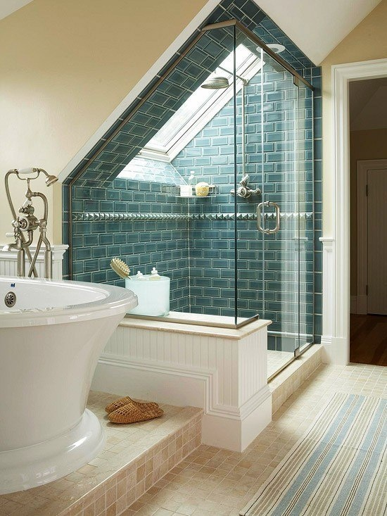 an attic bathroom with a shower space clad with blue tiles and a refined bathtub and a striped rug