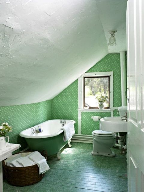 a grene attic bathroom done with wallpaper, a green wall and a green clawfoot tub plsu a basket for storage