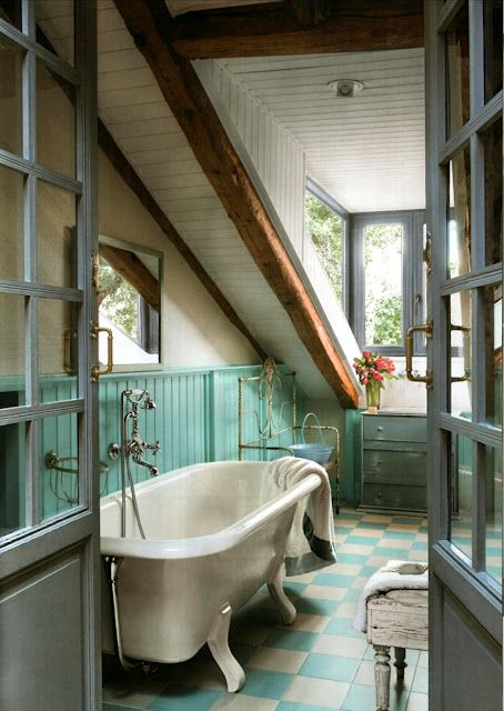 a colorful attic bathroom done with wooden beams, turquoise touches and a vintage tub