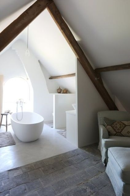 a small white attic bathroom with wooden beams, a tub and some shelves for storage