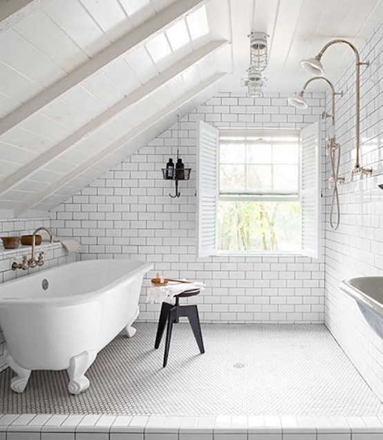 an airy white bathroom with subway and penny tiles and black grout, a clawfoot tub and a black stool