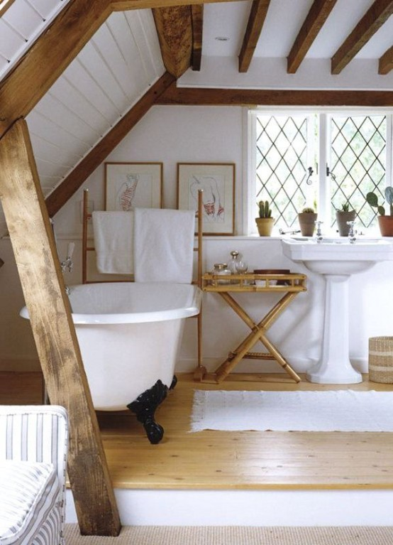 an attic rustic bathroom with wooden beams, a clawfoot tub, a free-standing sink and wooden furniture