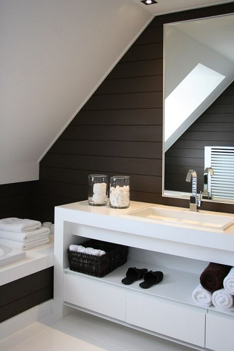 a minimalist contrasting bathroom in dark brown and white, with a large white vanity and white towels