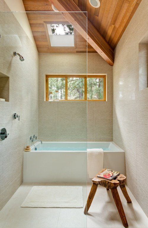 a neutral bathroom with textural tiles, a wooden ceiling and a stool, a shower space