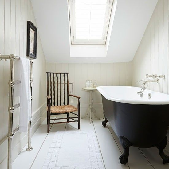 a neutral vintage attic bathroom with a skylight and a black clawfoot tub, a vintage chair