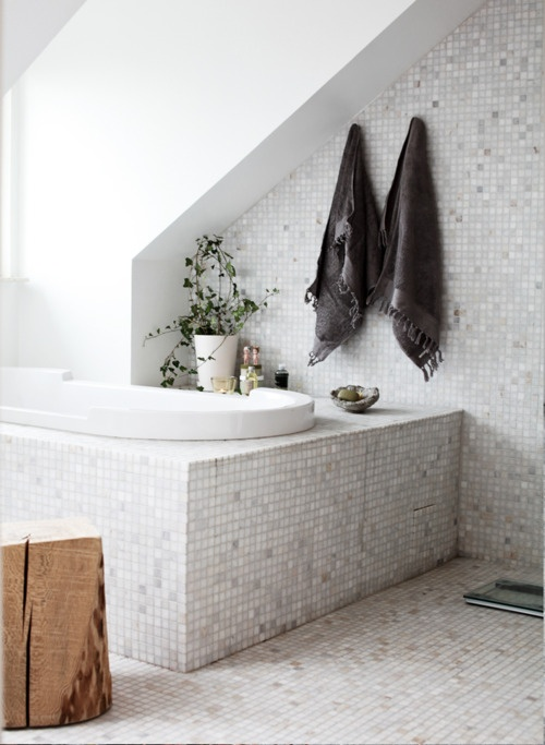 a neutral attic bathroom with a sunken tub, small scale tiles and a tree stump side table