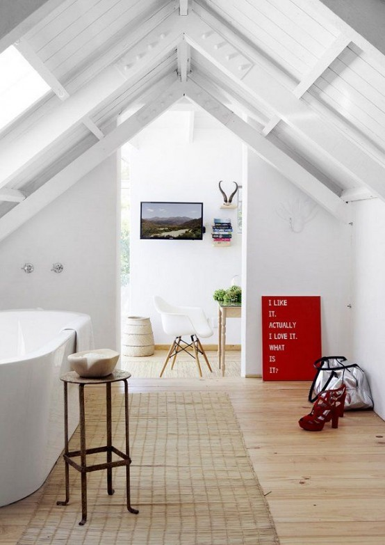 a white attic bathroom with an oval tub, some furniture and a jute rug, the space is flooded with light
