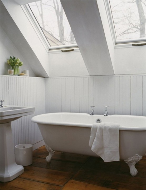 a white attic bathroom with skylights, a free-standing sink and a clawfoot tub