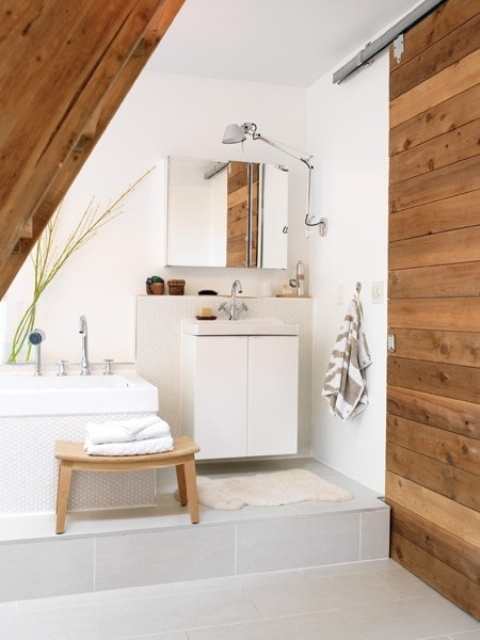 a neutrla bathroom with wodoen touches and furniture, a geometric tub and vanity