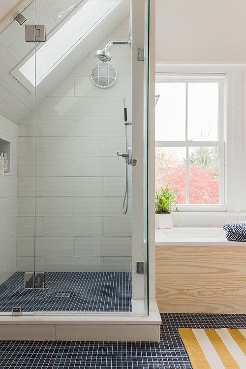 a shower space with navy tiles, a large storage unit under the windowsill