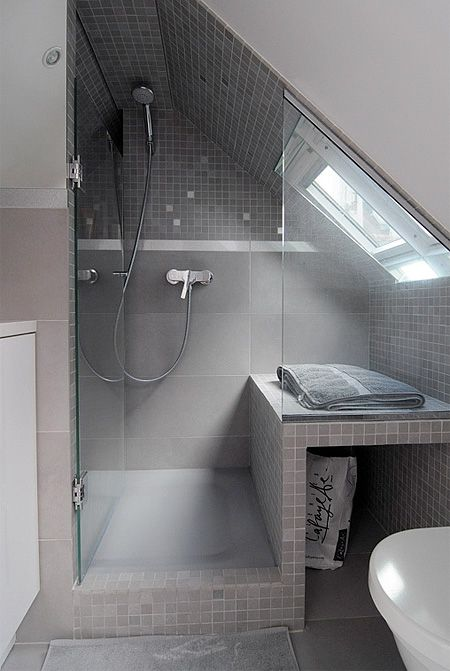 a neutral small attic bathroom with a skylight in the shower, grey and taupe tiles