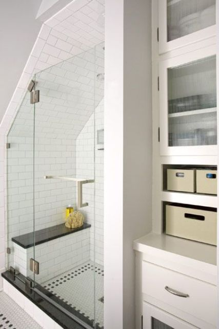 a neutral bathroom with closed storage drawers and units, subway and penny tiles in the shower space