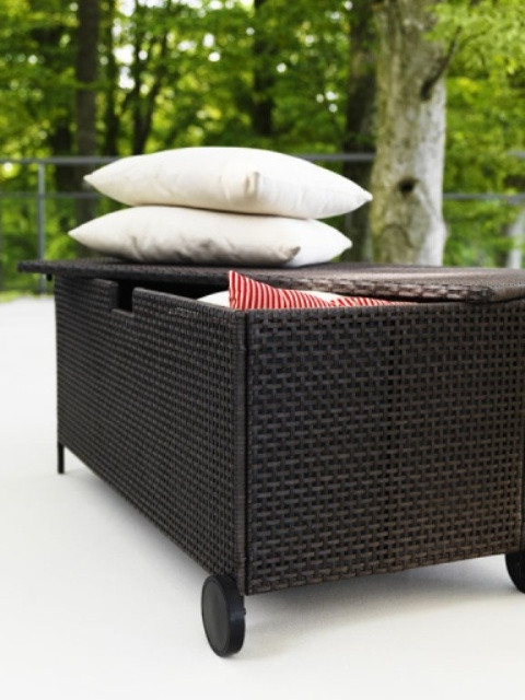 a black mobile bench withh storage space inside is a cool idea for a small balcony