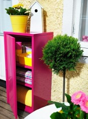 a bright pink cabinet for storage is a cool idea if you have not a veyr tiny balcony