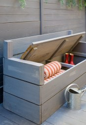 a grey painted wooden bench with storage space inside is an easy DIY project