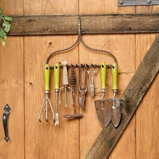 attach a piece of rake to the wall to use it as a holder and hanger for your tools