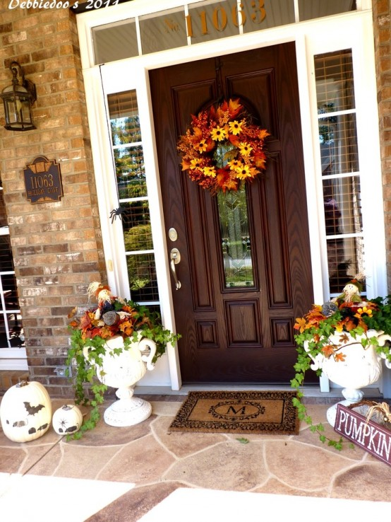 Plant seasonal blooms in creative planters and place them from both sides of the front door & 85 Pretty Autumn Porch Décor Ideas - DigsDigs Pezcame.Com