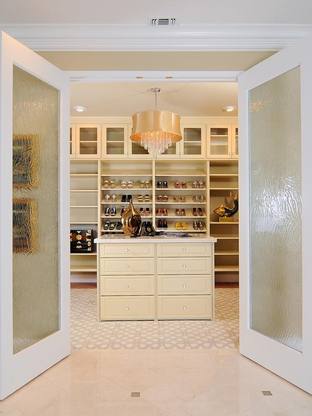 a neutral and glam walk in closet with lots of open storage units, a warm colored dresser, a polished pendant lamp and built in lights