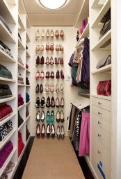 a modern neutral closet with open storage units and drawers and a large open shoe shelf in the center is a cool and bold idea