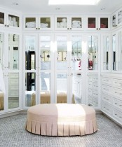 a beautiful feminine walk-in closet with mirror walls and drawers, with a pink ottoman in the center is a lovely idea