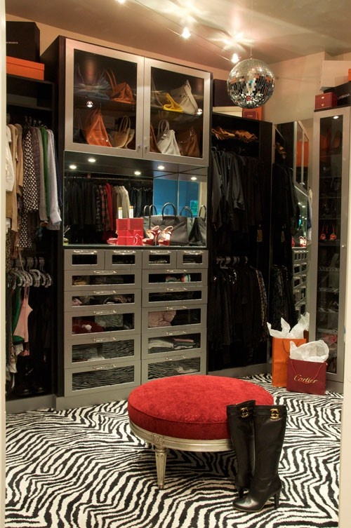 a catchy girlish closet with a disco ball, a zebra print rug, a deep red stool and silver storage units with glass doors is a bold idea