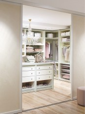 a lovely pastel feminine closet done in pastel green and pink, with a crystal chandelier and a large storage unit with drawers and an open storage unit