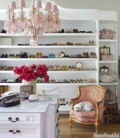 a stylish feminine closet with refined vintage touches, with long shelves and bag storage, with a dresser, a pink chandelier and a pink chair