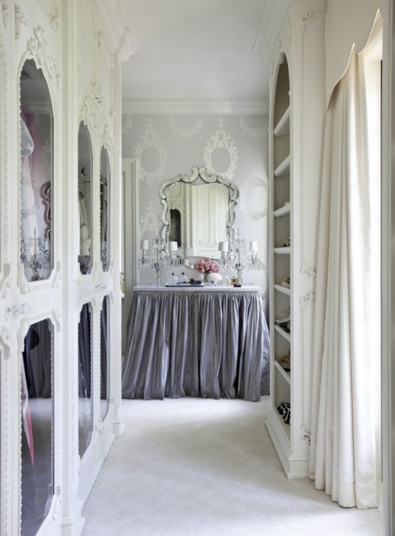 a delicate and girlish walk-in closet with white ornated frame and mirror doors plus an open storage unit and a vanity with a lilac skirt and a vintage mirror