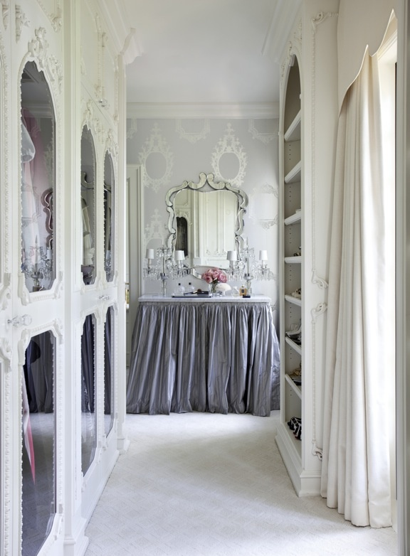 a delicate and girlish walk in closet with white ornated frame and mirror doors plus an open storage unit and a vanity with a lilac skirt and a vintage mirror