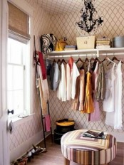 a pretty girlish walk-in closet with printed wallpaper, an open storage unit, a black crystal chandelier, a colorful geometric ottoman and a ladder