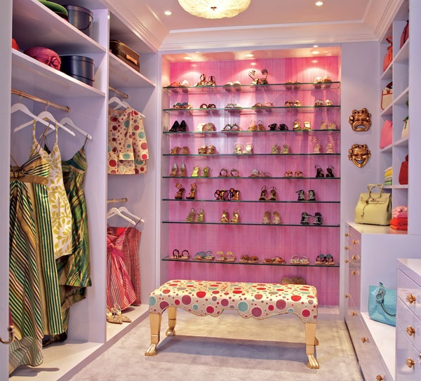 a bright and cool feminine closet with a pink accent wall and glass shoe shelves, lilac open storage units and a pretty polka dot bench is amazing