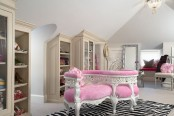 a pretty feminine walk-in closet with built-in storage units, a pink curved upholstered bench, a printed rug and some pink touches around