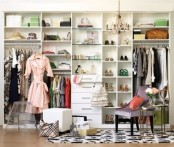 a pretty feminine walk-in closet with open shelves, a lilac chair, some stools and ottomans, a crystal chandelier and a printed black and white rug