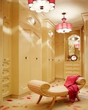 a cool warm-colored feminine closet with sleek storage units and drawers, a neutral printed daybed, touches of red – pendant lamps and a blanket