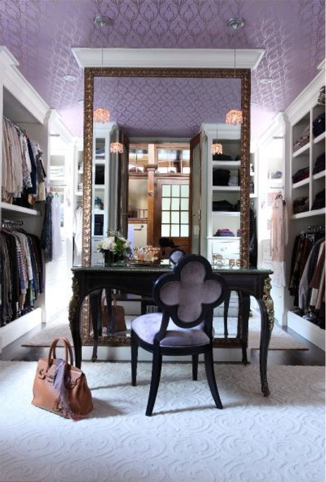 a vintage feminine walk in closet in lilc, with a lilac print wallpaper on the ceiling, open storage units around, a large mirror and a black vanity plus a lilac chair