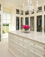 a pretty neutral walk-in closet with glass wardrobes and an oversized cabinet with lots of drawers for storing smaller stuff and accessories