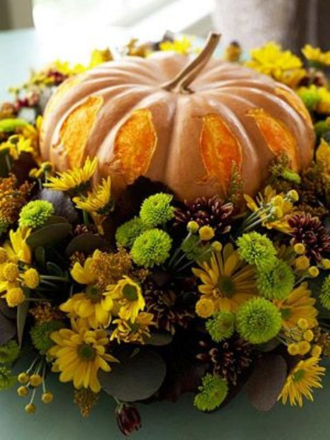 a bright fall centerpiece of a pumpkin with petals and super bright natural blooms and greenery wows