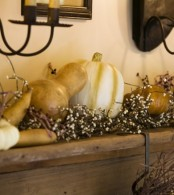 a mantel decorated with pumpkins and gourds plus blooms looks all-natural and very fall-like
