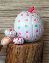 white pumpkins with bright yarn and bright polka dots plus a giant polka dotted one look veyr fun and whimsy